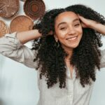 woman with long, brown curly hair smiles