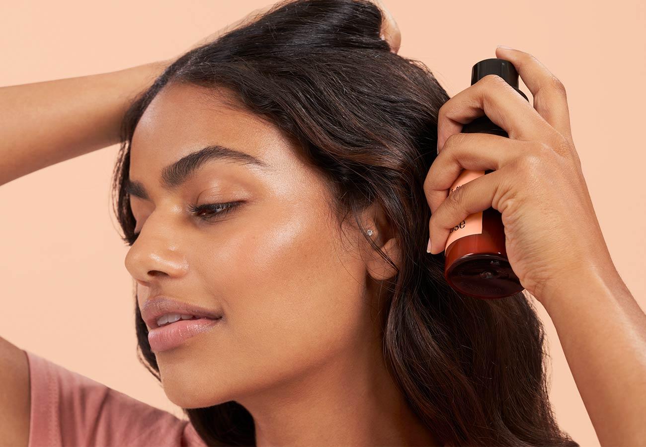 woman with long, dark hair using dry shampoo