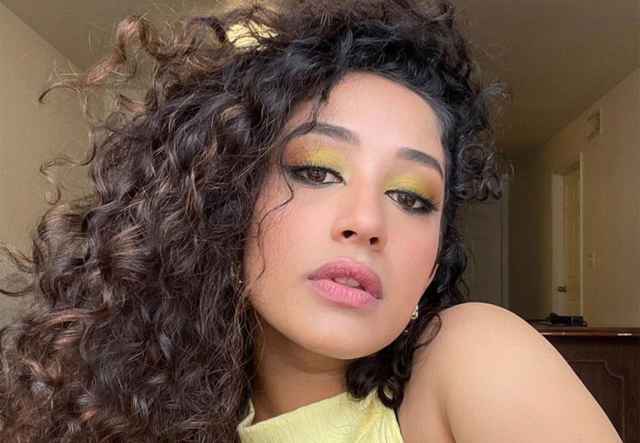 woman with brown, curly hair and a yellow top