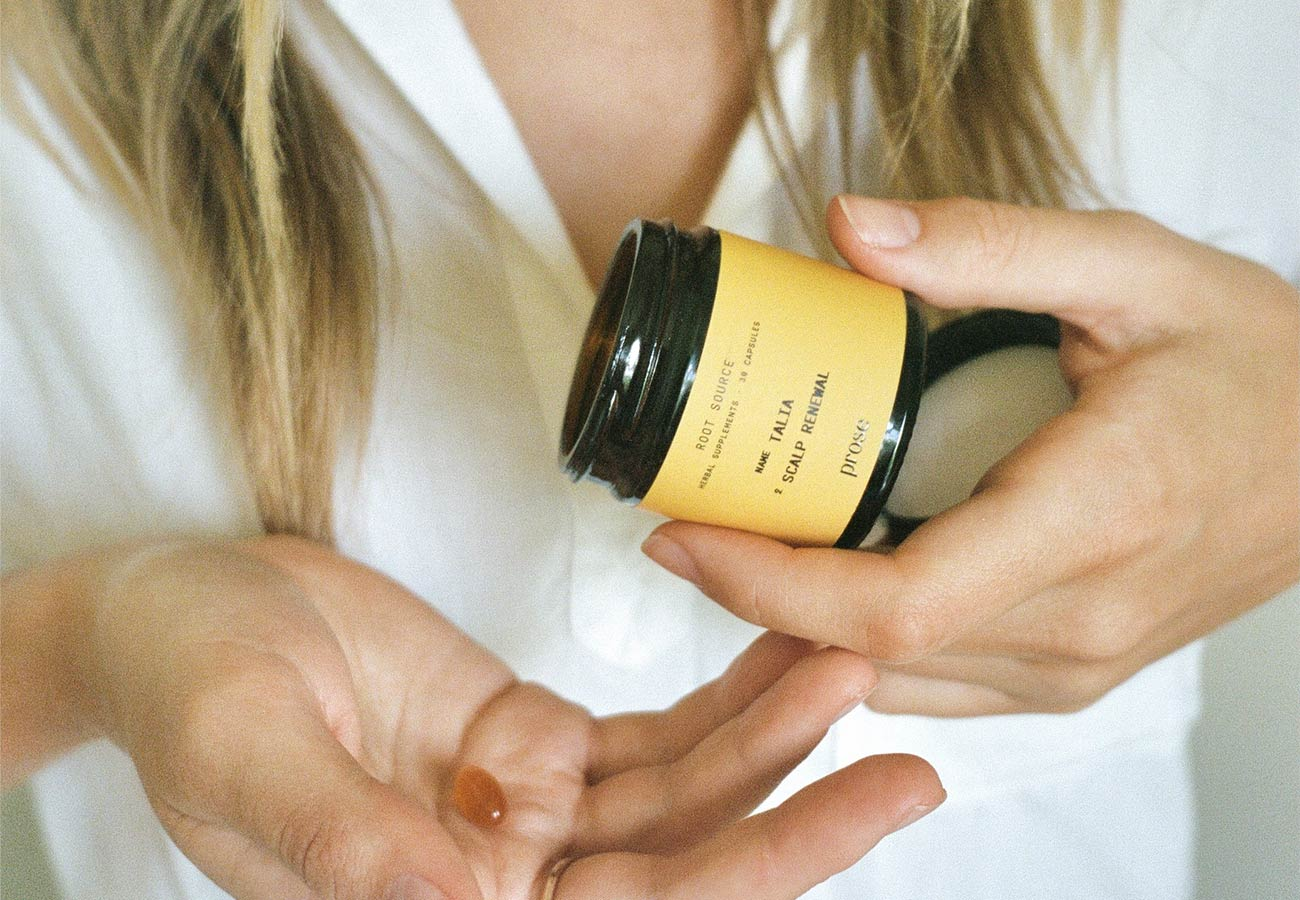 woman with blonde hair pouring out hair supplements