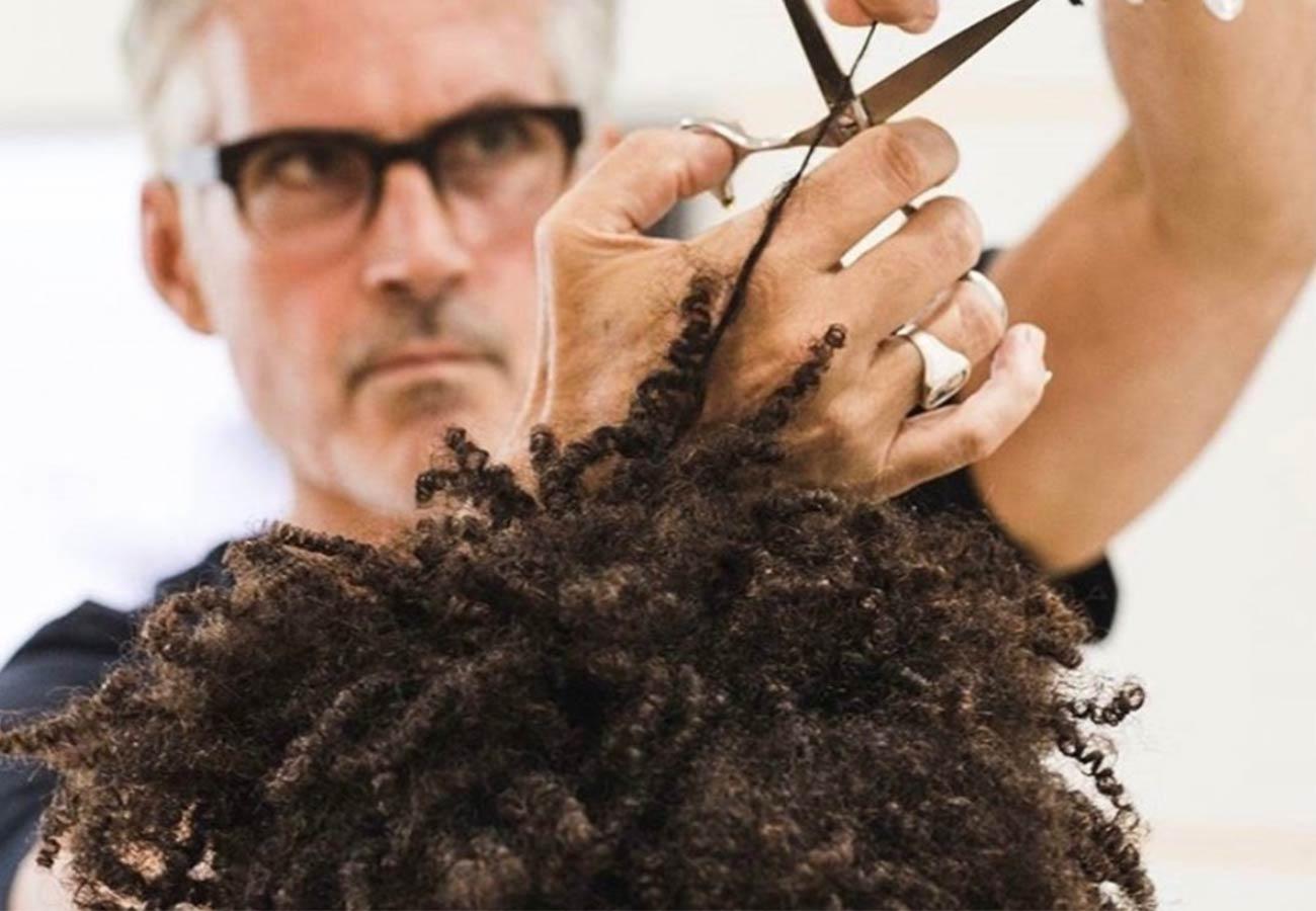 hairstylist cutting man's curly hair