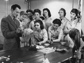 13th March 1957:  A BBC make-up man teaches a batch of new recruits the art of dressing hair for television appearances.  (Photo by William Vanderson/Fox Photos/Getty Images)
