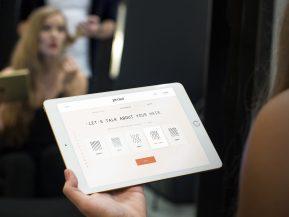 Woman at a hair consultation holding an iPad.