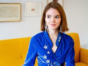 alice bell sits on a yellow couch wearing a blue dress