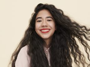 girl with long, brown curly hair smiles while wearing red lipstick