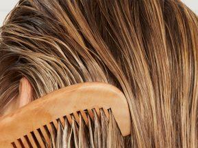woman with blonde hair runs a comb through her hair