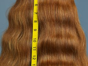 woman with red, wavy hair shows off her long hair next to measuring tape