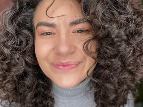 woman with dark curly hair with a few grey hairs