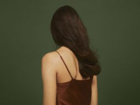 woman with long, brown hair stands against a dark, green backgorund