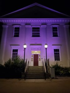 Image of Danvers Town Hall illuminated purple in honor of National Purple Heart Day