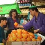 An Israeli fruit vendor sells oranges to a mother and her son
