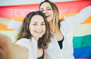 Two women take a selfie in front of a rainbow flag.