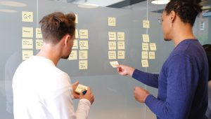 Two people collaborating over sticky notes on a wall.