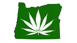 The state of Oregon in green with a white marijuana leaf in the center.