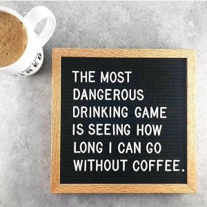 "Photograph of coffee cup with sign next to it reading ""The most dangerous drinking game is seeing how long i can go without coffee"""