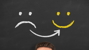 Stock photo of chalkboard with sad face and smiley face drawn in chalk