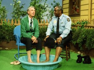 Fred Rogers and Francois Clemmens sit together with their feet in a kiddie pool.