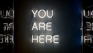 """A neon sign reads """"You Are Here."""""""