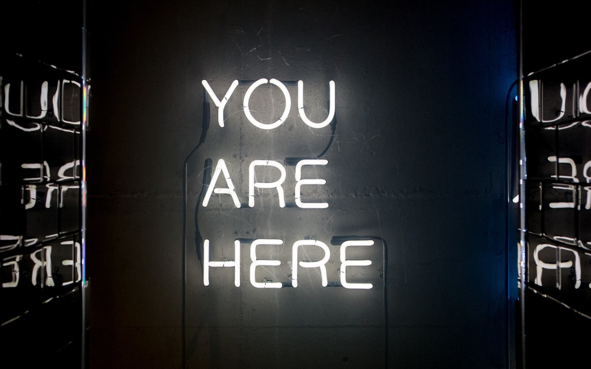 "A neon sign reads ""You Are Here."""