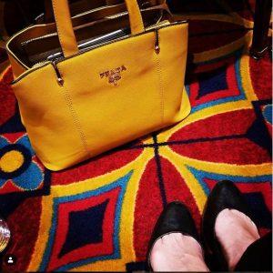 Yellow knock-off Prada purse on colorful carpet