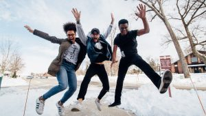 Three Young Adults Jumping in sync on Snow Plowed Sidewalk