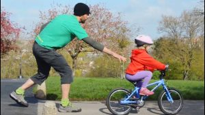 Dad teaching kid how to ride bike