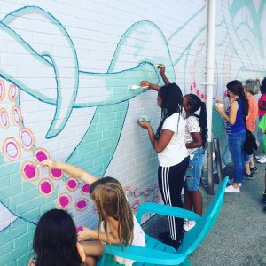 Kids painting the mural
