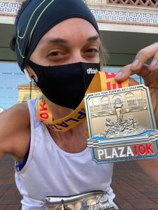 A woman holding up a 10k race medal