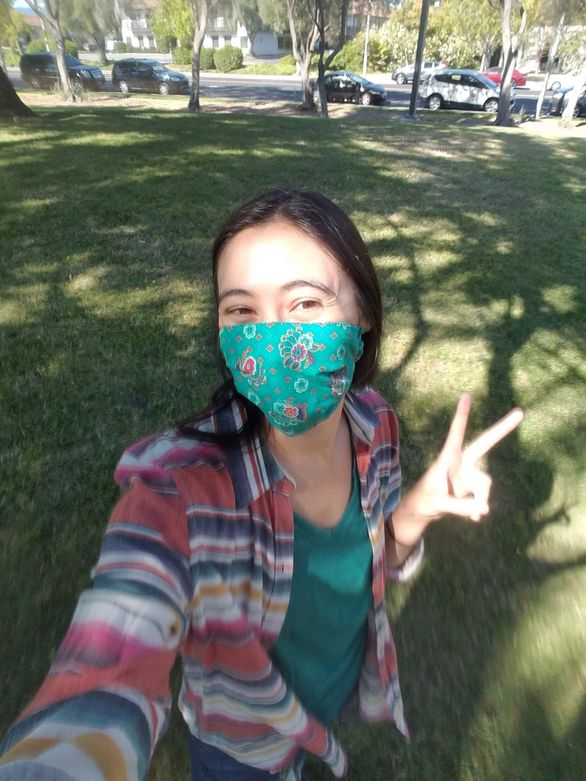 Woman in mask takes selfie in a yard while giving peace sign