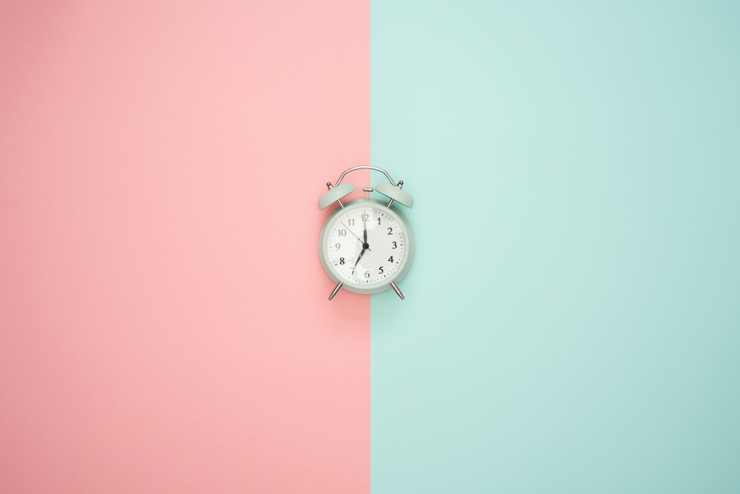 An alarm clock set against a pink and green backdrop