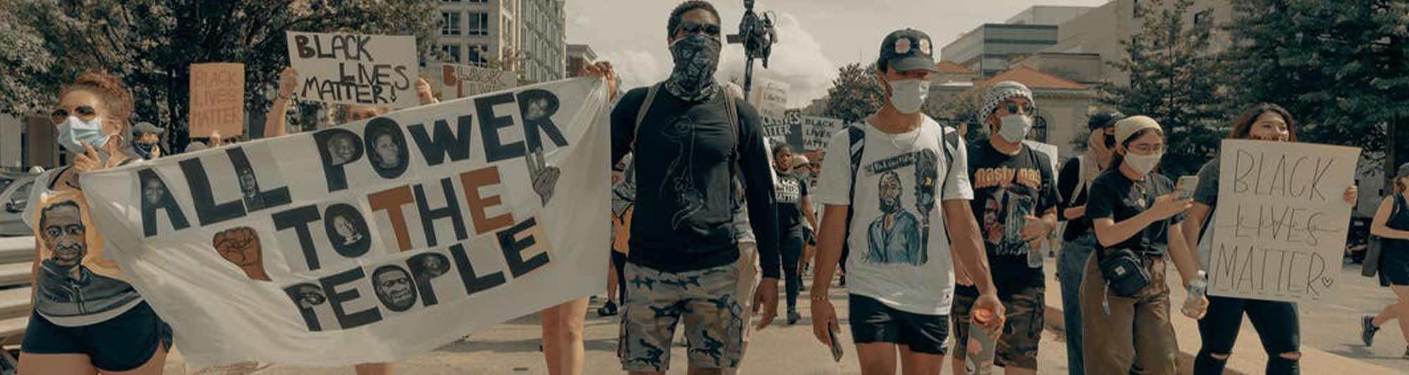 """People wearing masks, marching in peace, holding signs that say """"All the Power to the People"""" and """"Black Lives Matter"""""""