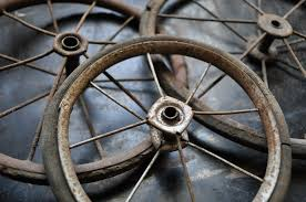 image is of three antique brown spoked wheels