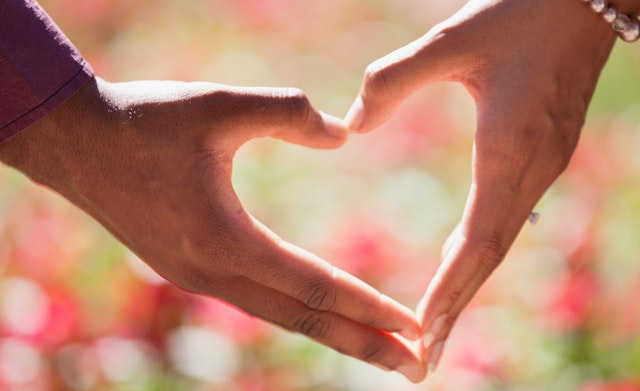 Two hands forming a heart with a floral background.
