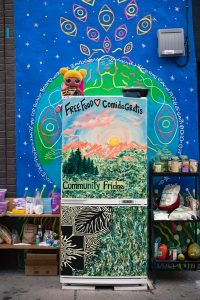Painted community fridge in front of a mural of the Earth.