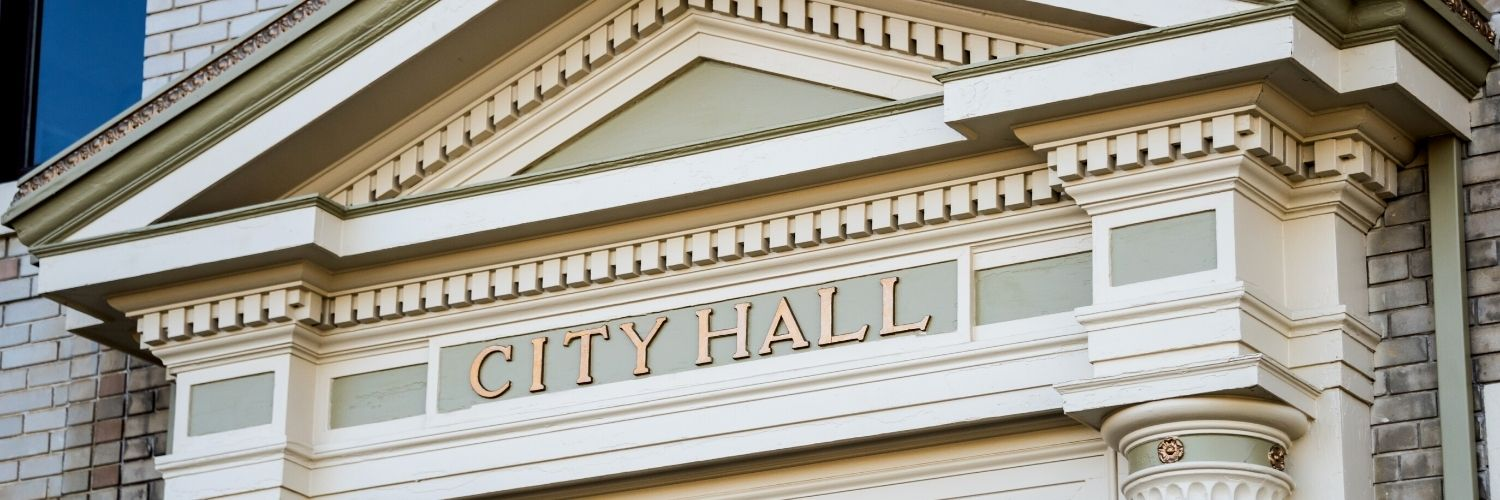 Exterior of classic style building with City Hall sign
