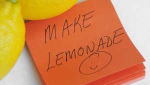 """Two lemons with a sticky note that has a handwritten note that says """"Make Lemonade"""" and a smiley face."""