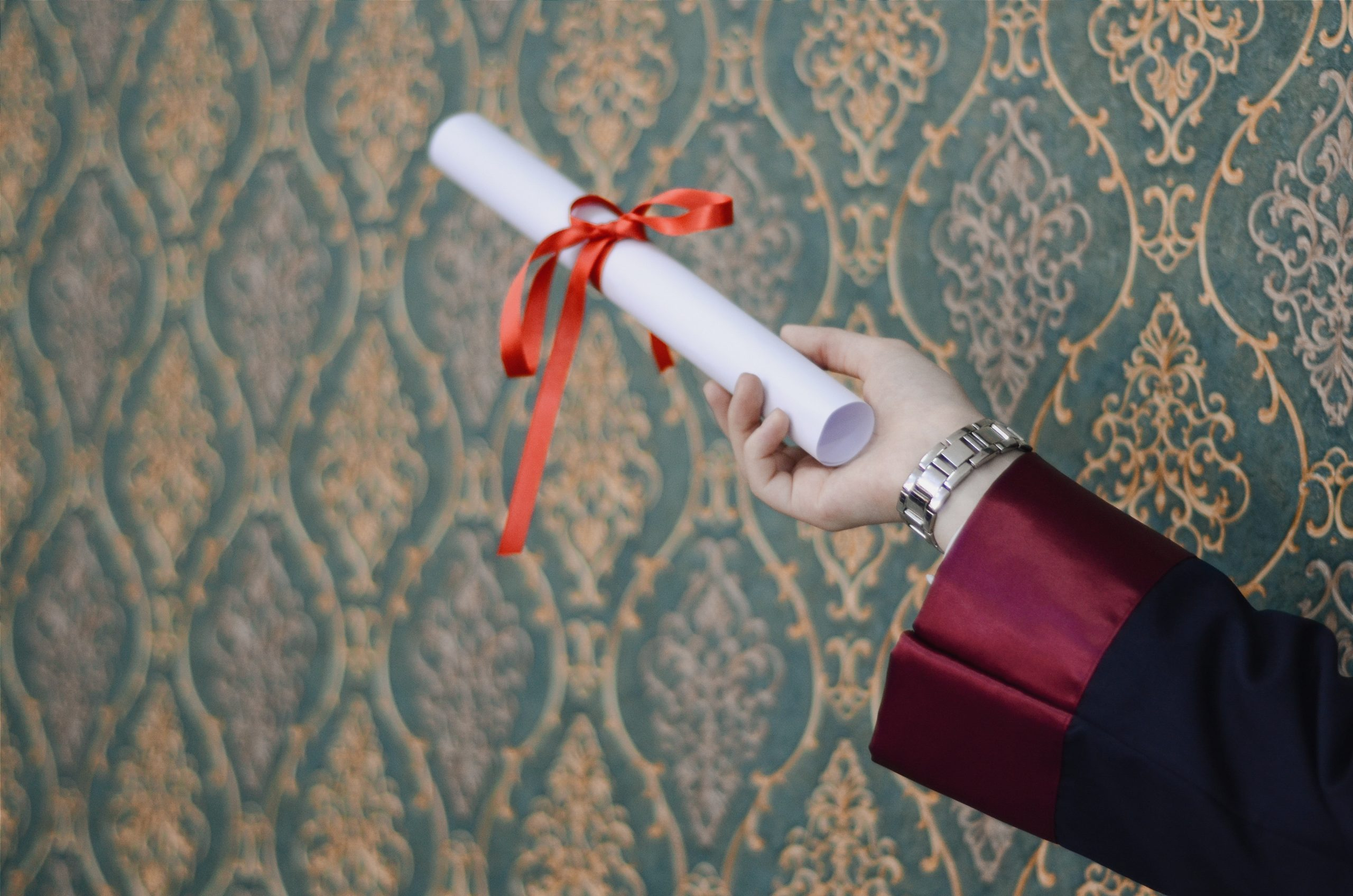 arm holding a diploma with a ribbon