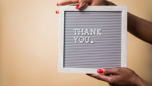 Female hands hold a sign board with the text Thank You in small letters.