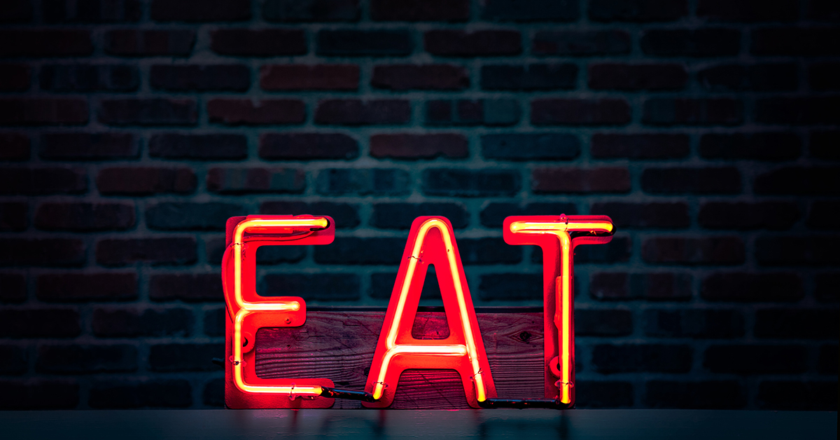 """A red neon sign of the word """"Eat"""" against a brick backdrop in a darkened room."""