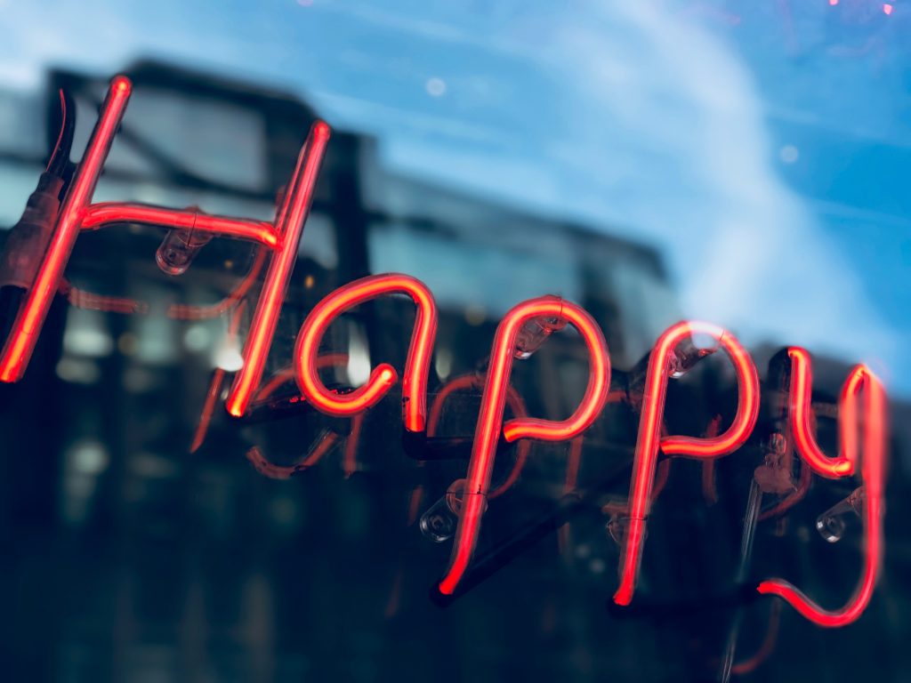 A neon sign that says Happy