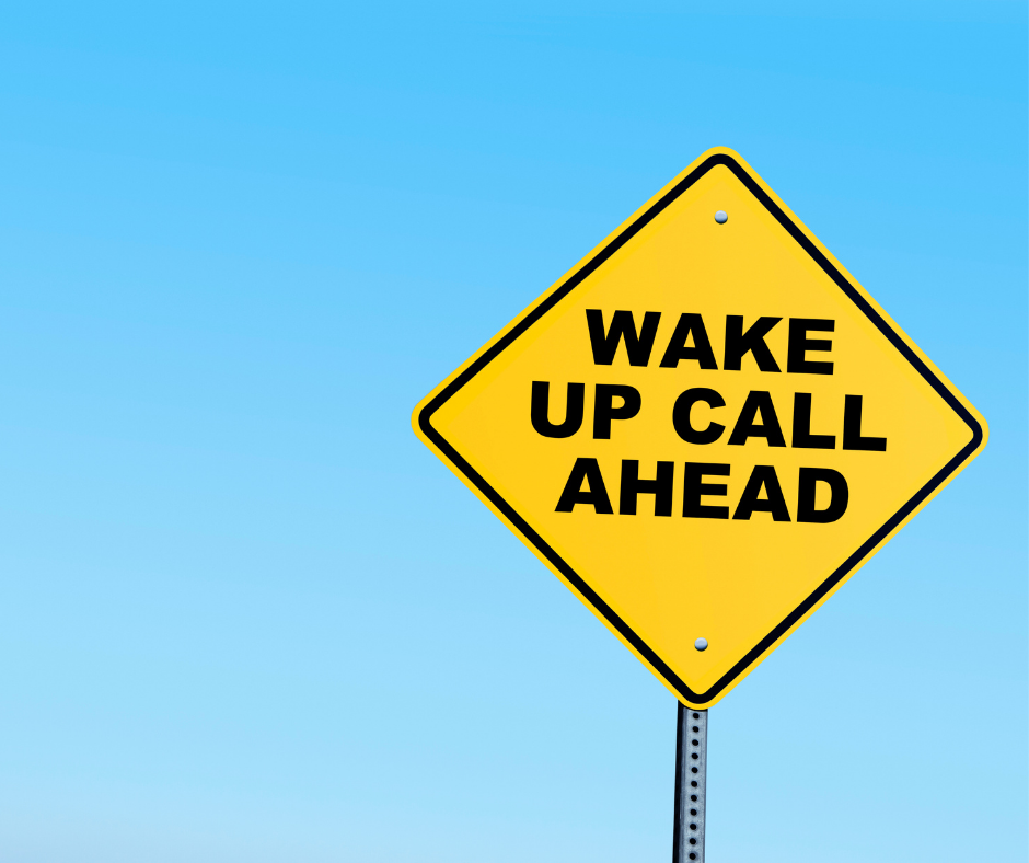 Yellow signs with black text that says wake up call ahead