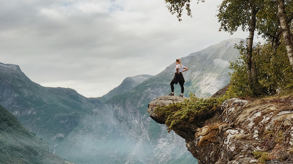 Woman standing on the edge of a cliff with mountains in the background.