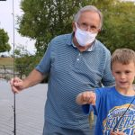 man and boy with fishing rods