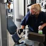 woman cleaning fitness equipment