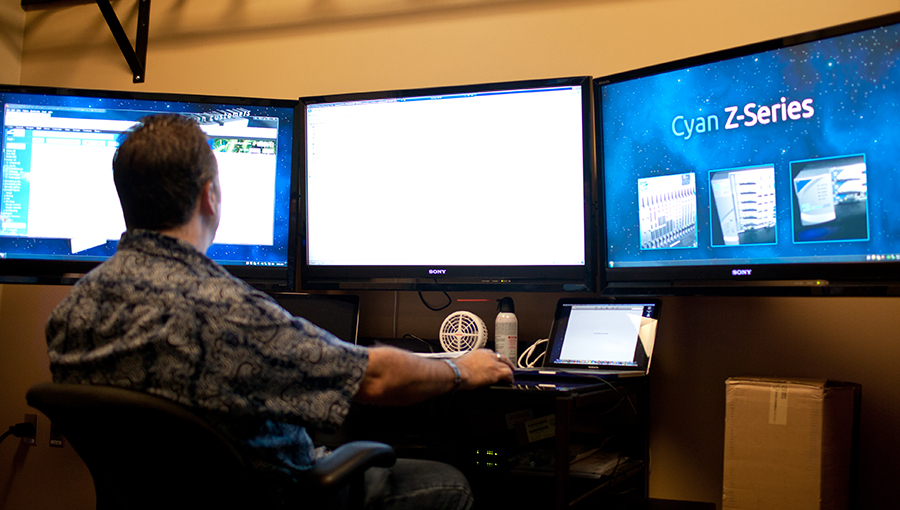 photo of IT person working at large computer screens
