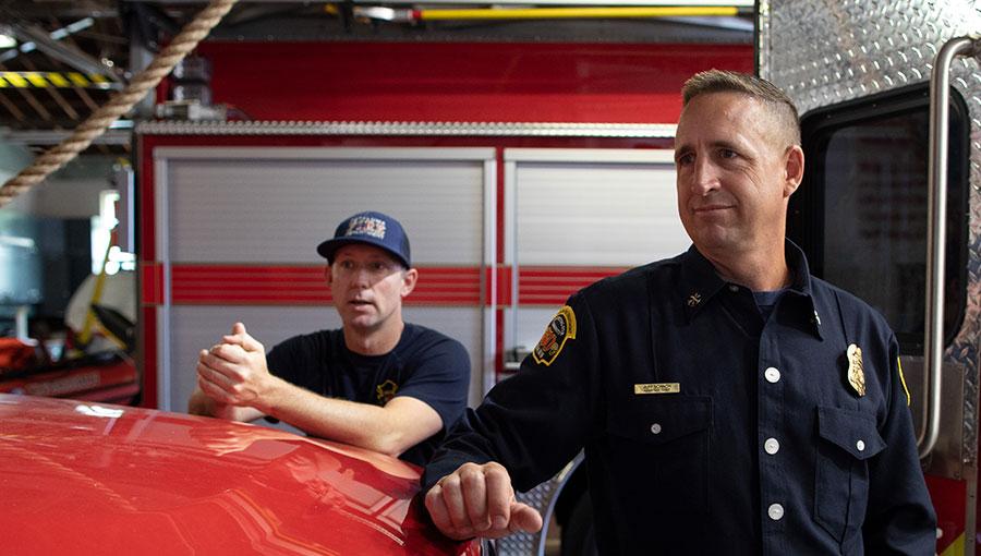 photo of fireman next to fire truck