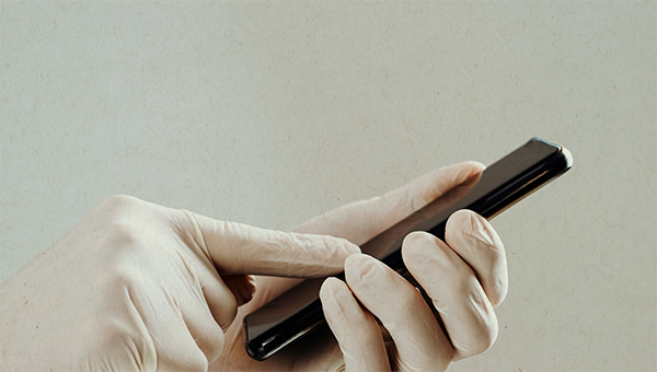 picture of a gloved hand using phone