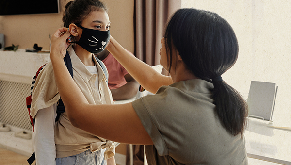 mom putting mask on child