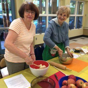 2 women preparing dough to bake