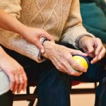elderly man holding yellow and blue ball while woman gently touching mans wrist